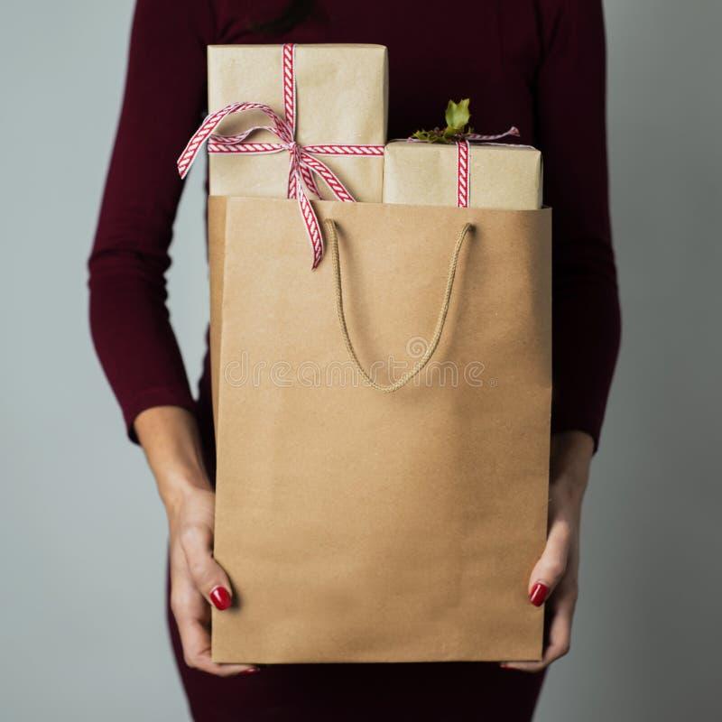 Kvinna med en shoppingpåse mycket av gåvor arkivbild