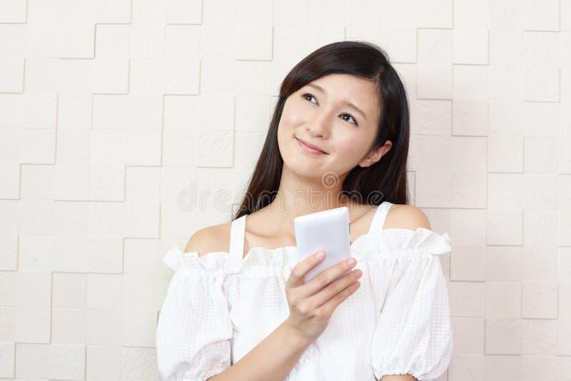 Kvinna med en smart telefon arkivfoton
