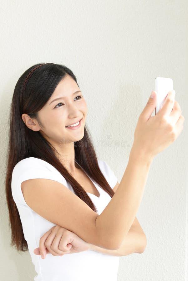 Kvinna med en smart telefon royaltyfri foto