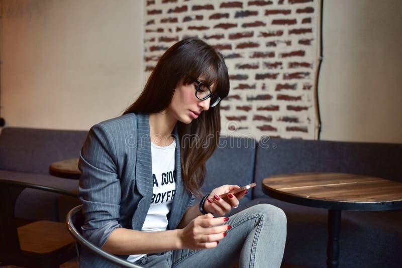 Kvinna med en telefon i ett kafé arkivfoto