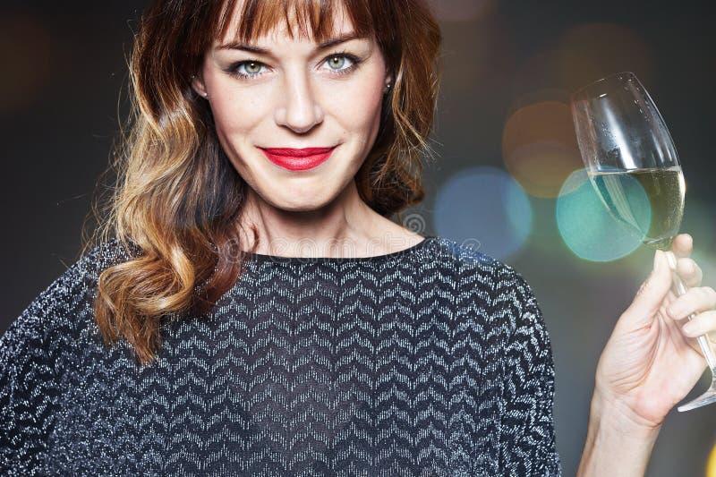 Kvinna med ett exponeringsglas av champagne på mörk bakgrund med signalljus och bokeh Dam med långt lockigt hår som firar och att royaltyfri foto