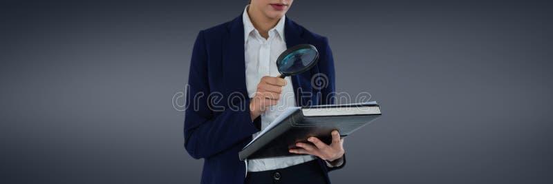 Kvinna med ett förstoringsglas mot grå bakgrund som att söka efter ett försäkringbegrepp arkivbilder