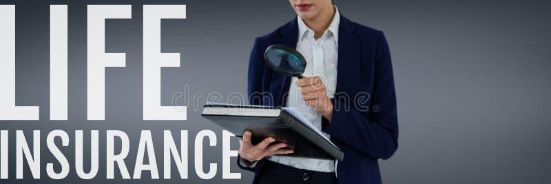 Kvinna med ett förstoringsglas mot grå bakgrund som att söka efter ett livförsäkringbegrepp arkivbilder