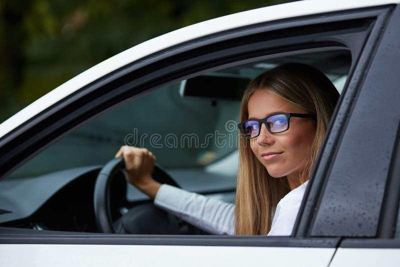 Kvinna med exponeringsglas som kör hennes bil royaltyfria bilder