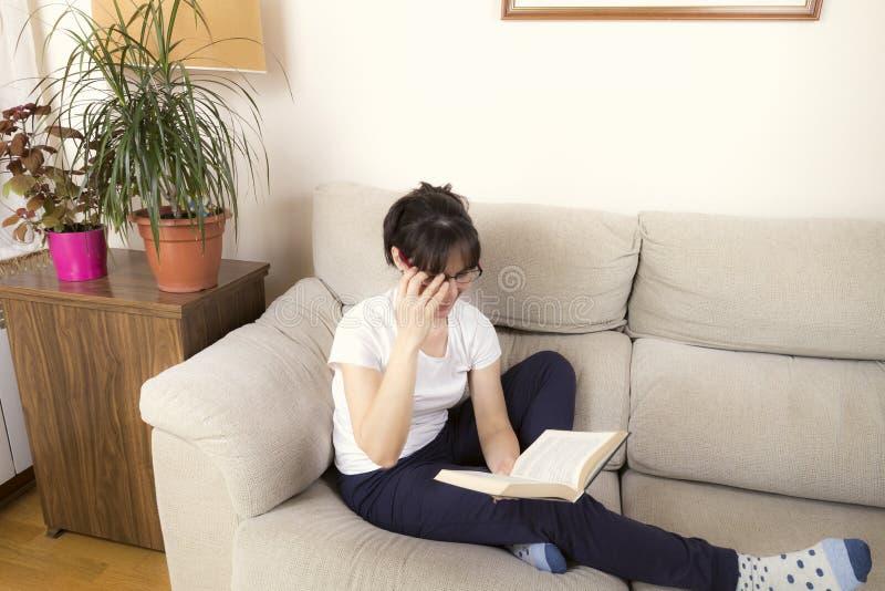 Kvinna med exponeringsglas som läser en bok på en soffa arkivbild