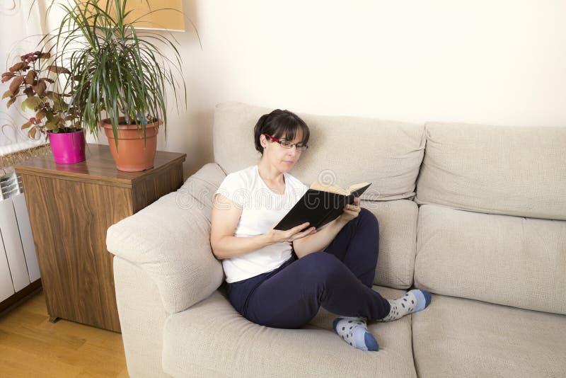 Kvinna med exponeringsglas som läser en bok på en soffa arkivbilder