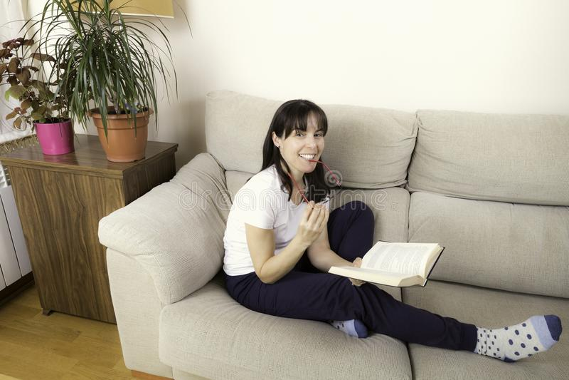 Kvinna med exponeringsglas som läser en bok på en soffa fotografering för bildbyråer