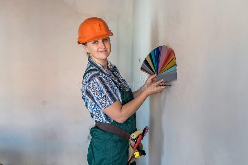 Kvinna med färgprovkarta som väljer färg för att måla väggar royaltyfri fotografi