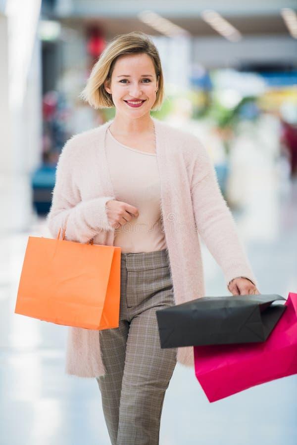Kvinna med färgrika shoppingpåsar som går i modern galleria royaltyfri foto