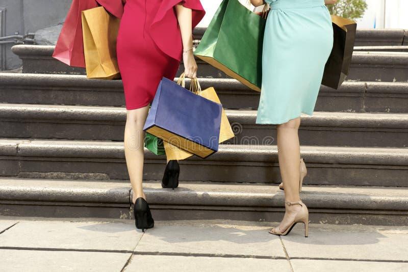 Kvinna med färgrika shoppingpåsar som går upp trappa royaltyfri bild