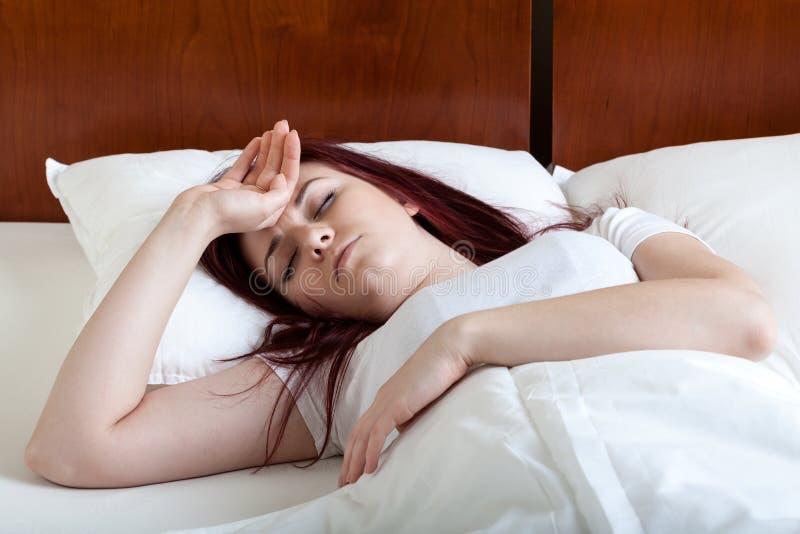 Kvinna med feber som ligger i säng arkivfoto