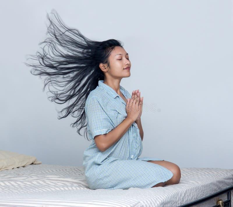 Kvinna med flyghår som ber i säng arkivbilder