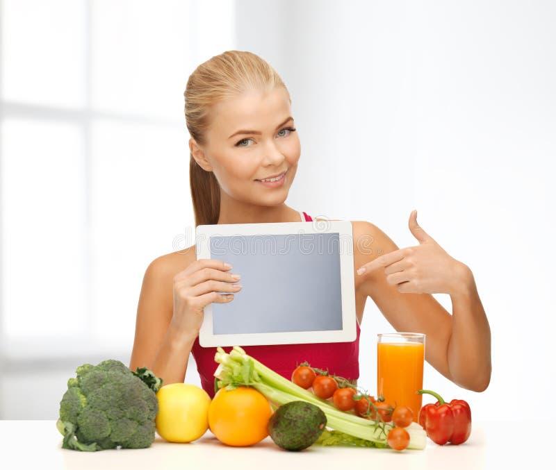 Kvinna med frukter, grönsaker och minnestavlaPC arkivbild