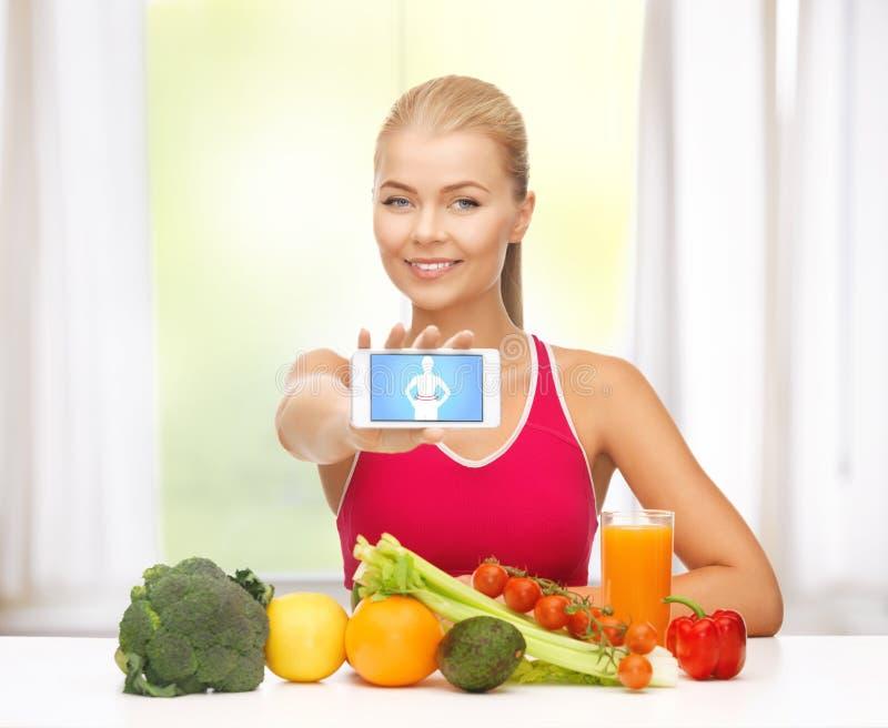 Kvinna med frukter, grönsaker och smartphonen fotografering för bildbyråer