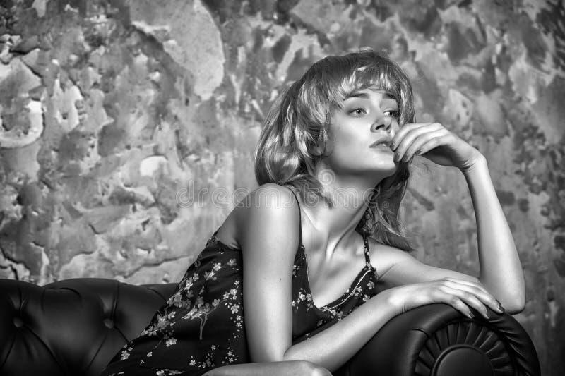 Kvinna med fundersamt uttryckssammanträde på lädersoffan Flicka i blond peruk med den nostalgiska blicken, minnesbegrepp royaltyfri fotografi