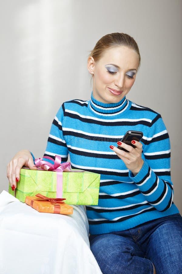 Kvinna med gåvaasken genom att använda smartphonen fotografering för bildbyråer