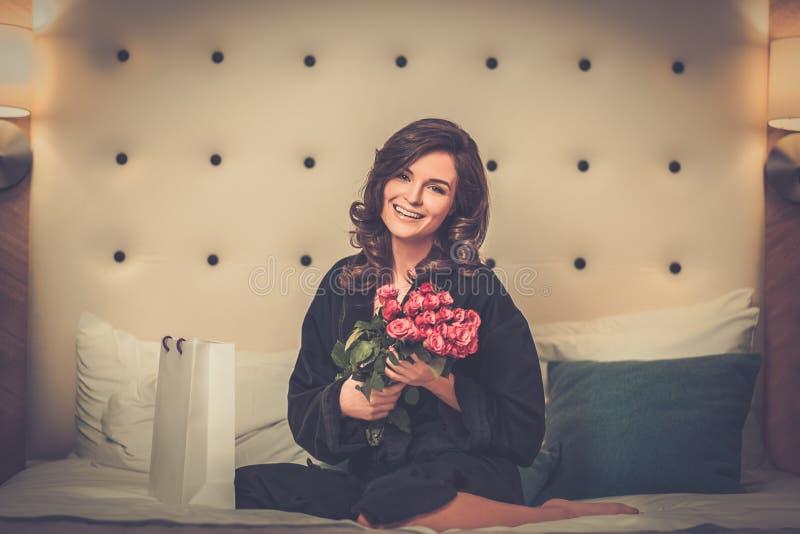 Kvinna med gåvan på en säng i hotellrum royaltyfri fotografi