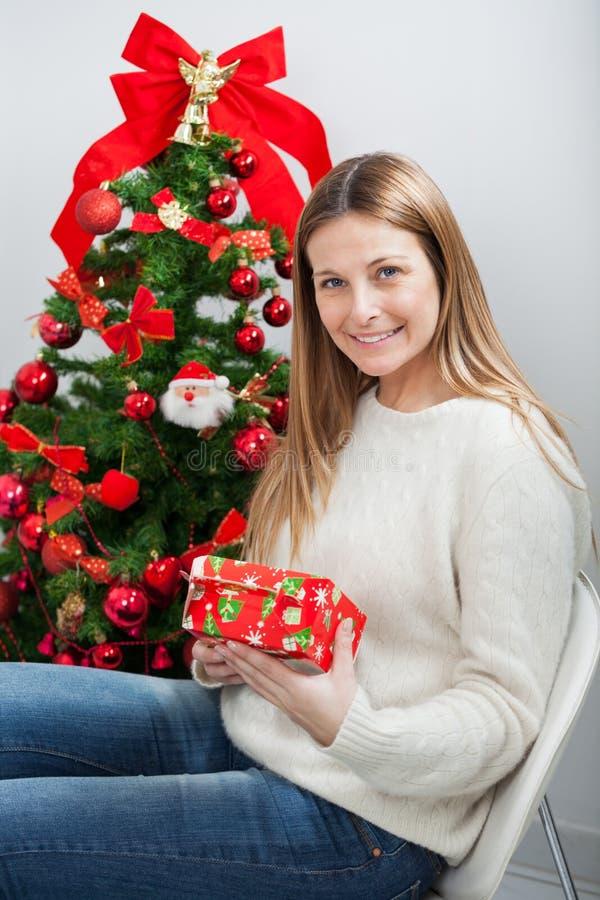 Kvinna med gåvasammanträde vid julgranen royaltyfria bilder