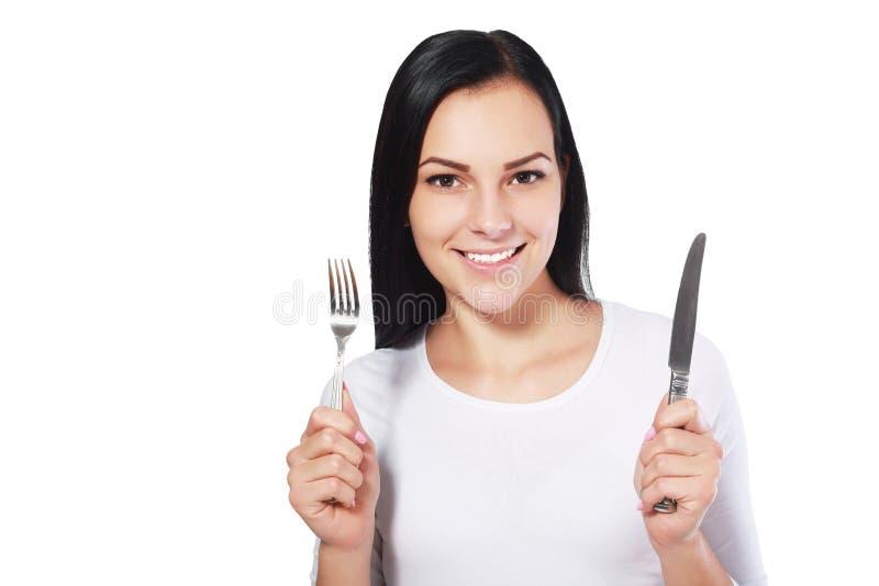 Kvinna med gaffeln och kniven arkivbild