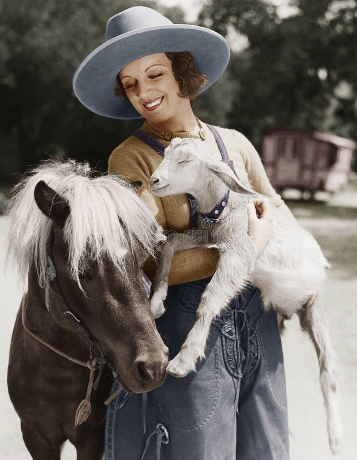 Kvinna med geten och ponny (alla visade personer inte är längre uppehälle, och inget gods finns Leverantörgarantier att det ska f fotografering för bildbyråer