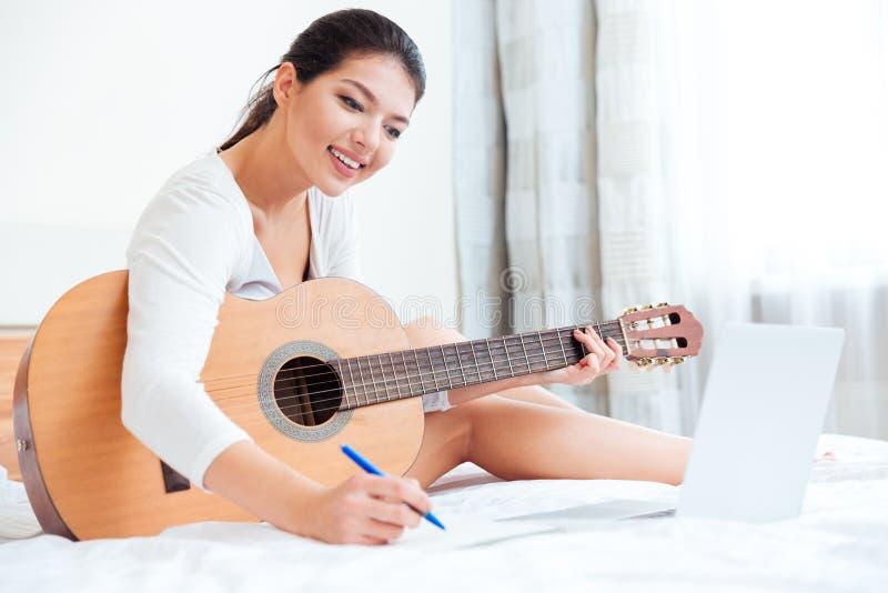 Kvinna med gitarrsammanträde- och danandeanmärkningar i notepad arkivfoton