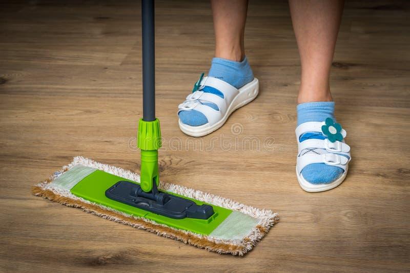 Kvinna med golvmoppet som moppar trälaminatgolvet royaltyfri fotografi