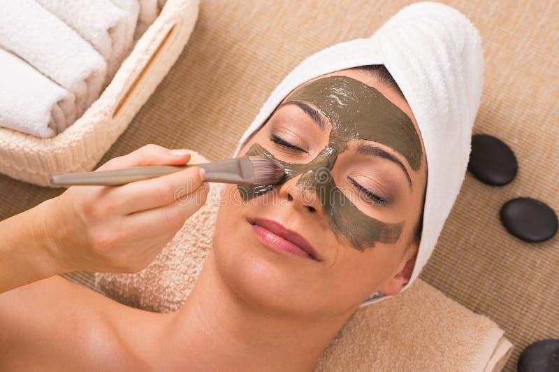 Kvinna med gröna Clay Mask At Spa royaltyfri foto