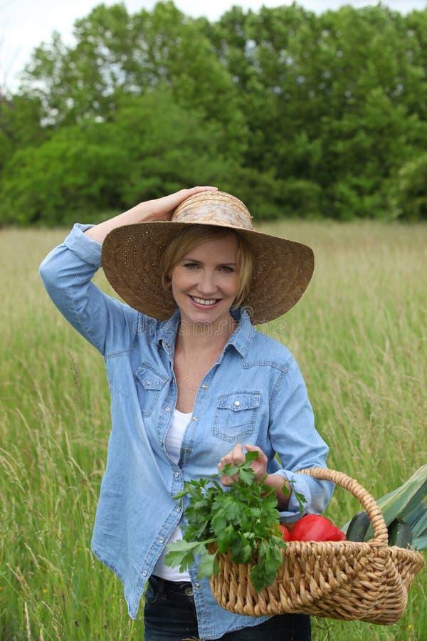 Kvinna med grönsakkorgen fotografering för bildbyråer