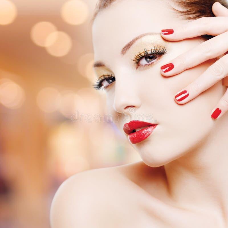 Kvinna med guld- glamourmakeup och röd manikyr royaltyfria bilder