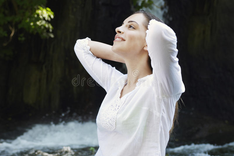 Kvinna med händer bak huvudet mot vattenfallet royaltyfria foton