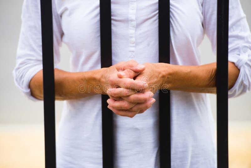 Kvinna med händer bak stänger i fängelse arkivbild