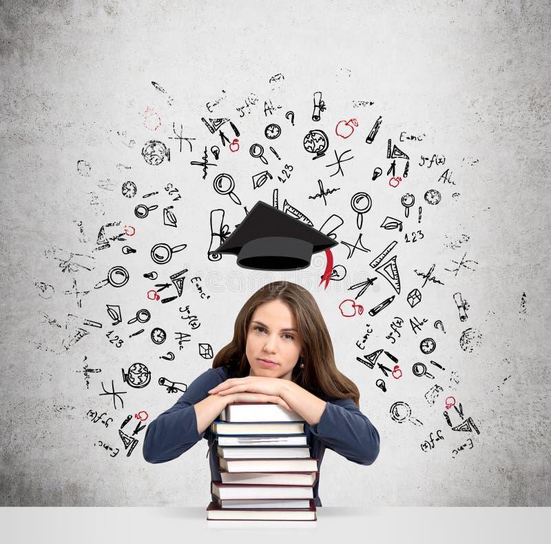 Kvinna med händer och huvudet på högen av att tänka för böcker royaltyfri foto