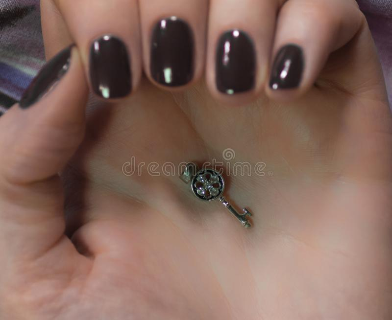Kvinna med härliga manicured svarta fingernaglar som korsar behagfullt hennes händer för att visa dem till tittaren på en röd bak royaltyfri fotografi