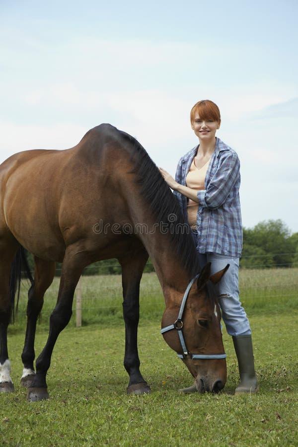 Kvinna med hästen i fält royaltyfri fotografi