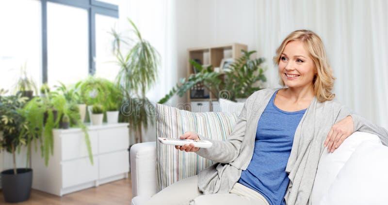 Kvinna med h?llande ?gonen p? tv f?r fj?rrkontroll hemma royaltyfria bilder