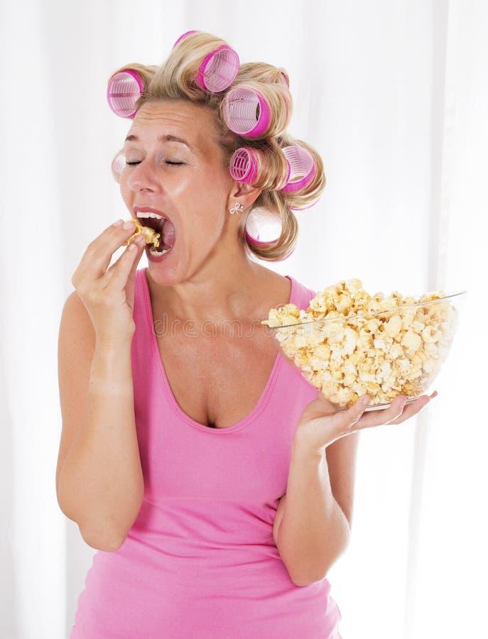 Kvinna med hårrullar som äter popcorn royaltyfria foton