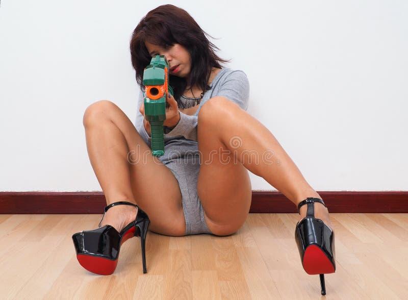 Kvinna med höga häl som siktar med leksakvapnet royaltyfri foto