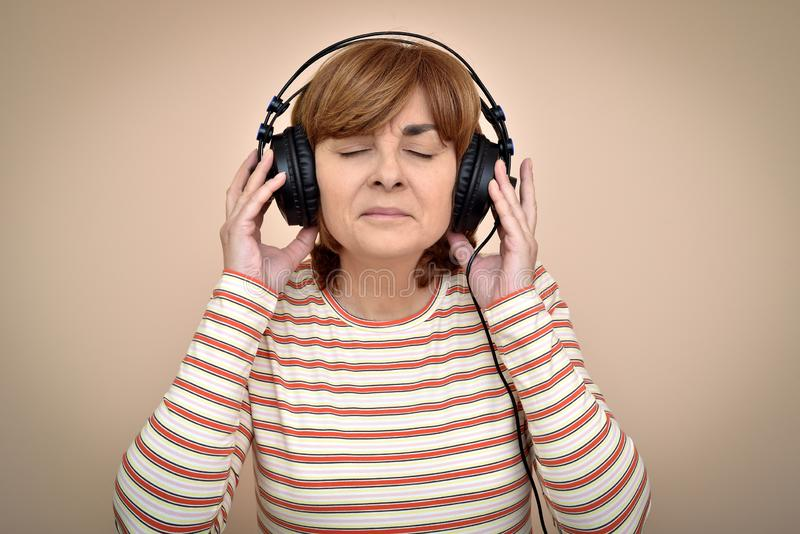 Kvinna med hörlurar och stängda ögon som tycker om musik arkivfoto