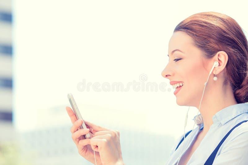 Kvinna med hörlurar som rymmer genom att använda den smarta mobiltelefonen royaltyfria bilder