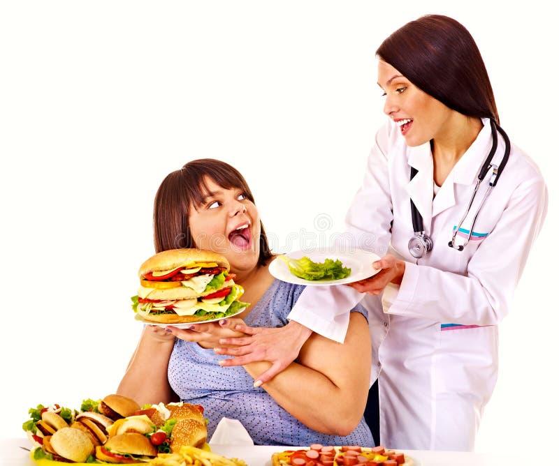 Kvinna med hamburgaren och doktorn. arkivbilder