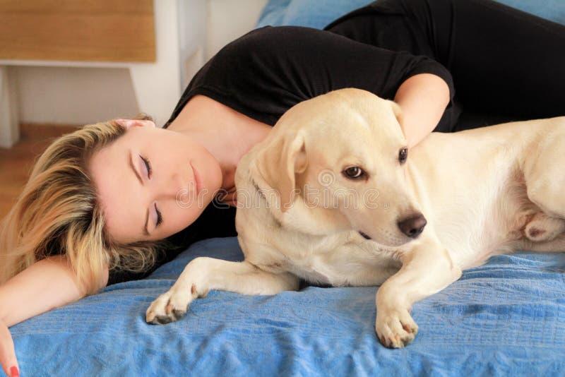 Kvinna med hemmastadd gullig hundkapplöpning Stilig flicka som vilar och sover med hennes hund i säng i sovrum Ägare och hund som royaltyfri fotografi