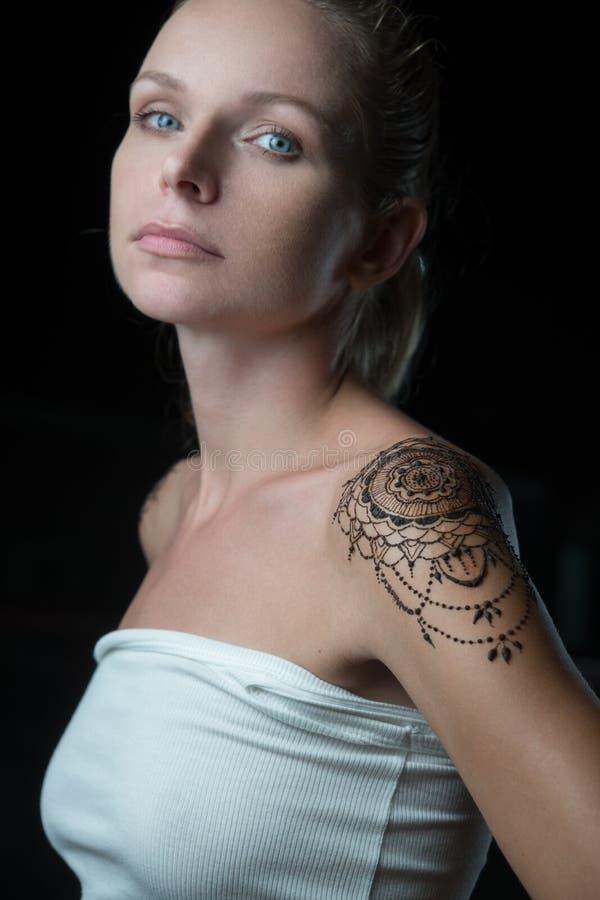 Kvinna med hennatatueringen på hennes skuldra arkivbilder