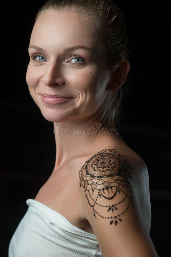 Kvinna med hennatatueringen på hennes skuldra arkivbild