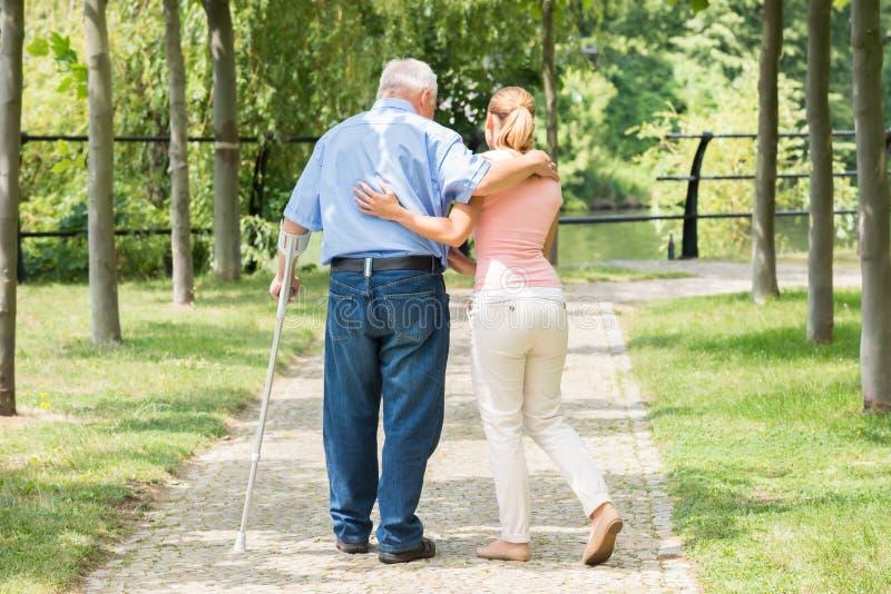 Kvinna med henne rörelsehindrad fader Standing In Park arkivfoton