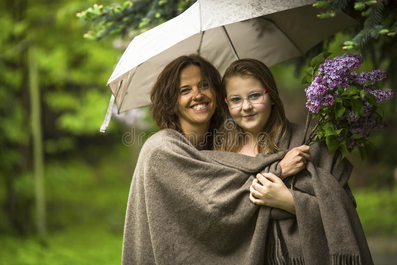 Kvinna med hennes dotter under ett paraply i parkera i regnet Förälskelse royaltyfria bilder