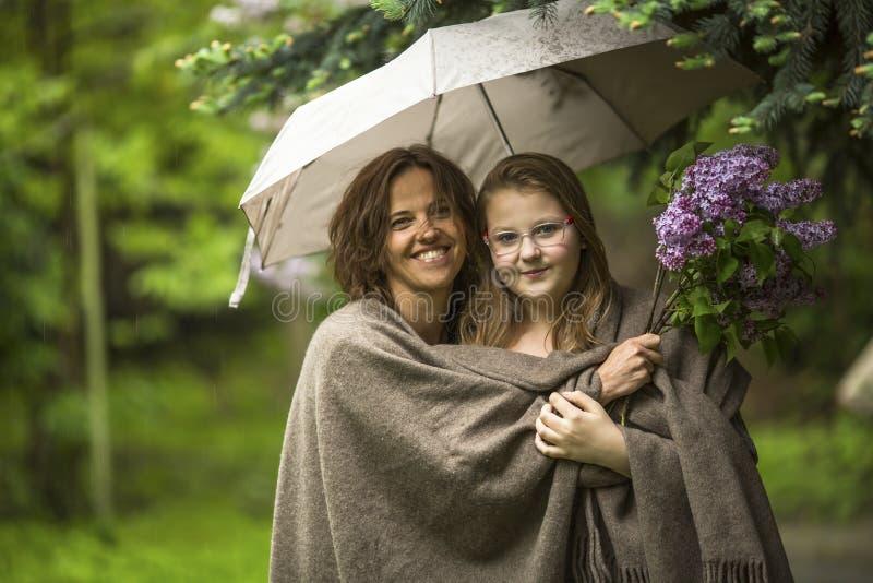 Kvinna med hennes dotteranseende i parkera under ett paraply Förälskelse royaltyfri bild