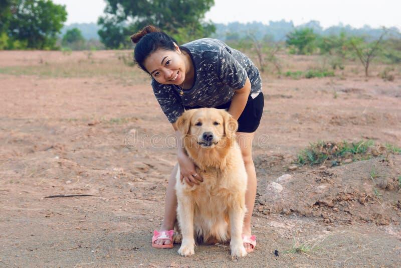 Kvinna med hennes golden retrieverhund som utomhus spelar royaltyfri bild