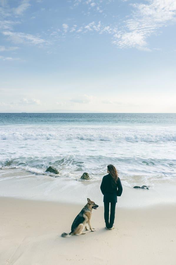 Kvinna med hennes hund på stranden arkivfoto