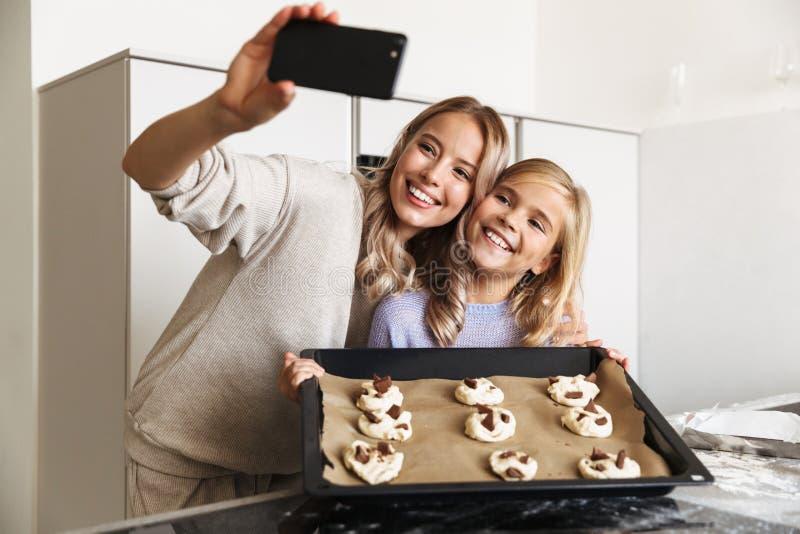 Kvinna med hennes lilla för syster som hemmastadda kök inomhus lagar mat raringbagerit för att ta ett foto vid telefonen royaltyfria foton