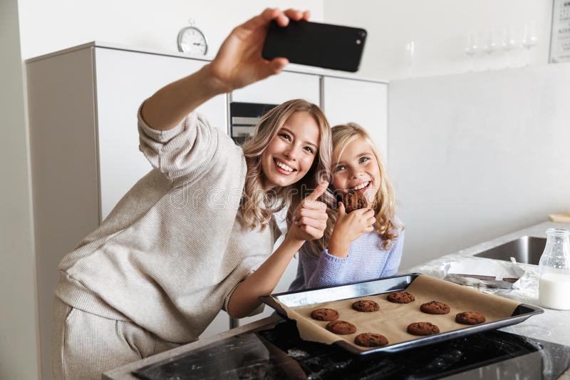 Kvinna med hennes lilla för syster som hemmastadda kök inomhus lagar mat raringbagerit för att ta ett foto vid telefonen royaltyfria bilder